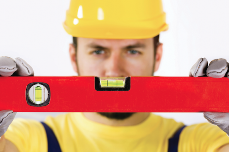 construction worker holding spirit level