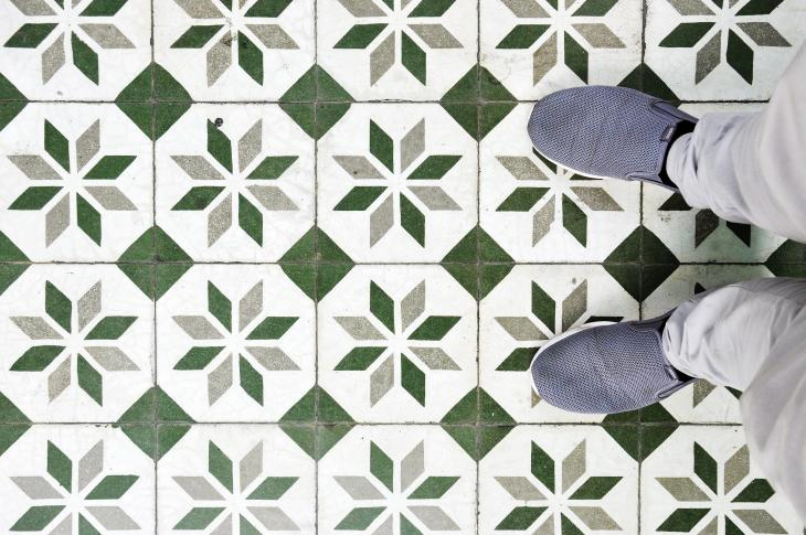 Patterned tile floor with person standing on it