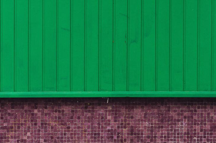 Green siding over brick wall