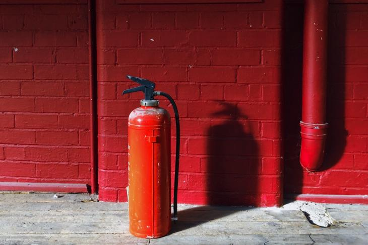 Fire extinguisher on floor against red wall