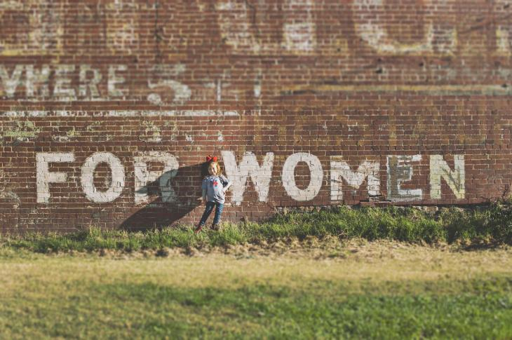 """Little girl in front of brick wall that says """"for women"""""""