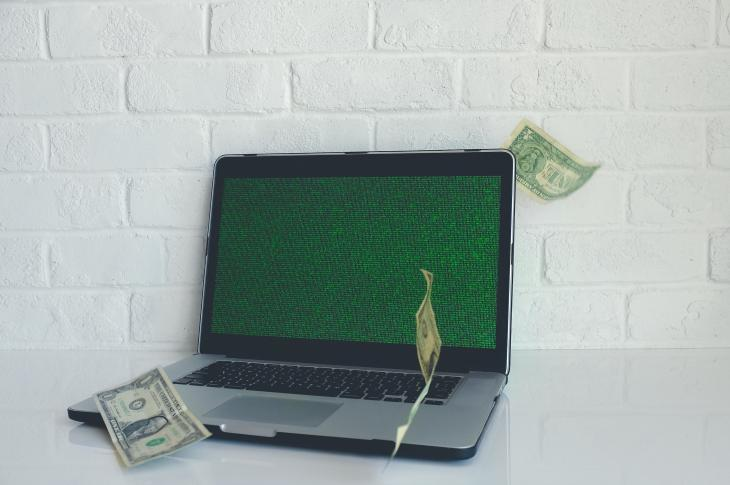 Laptop computer with dollar bills