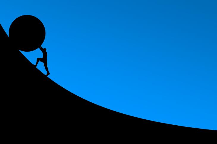 Man rolling rock uphill