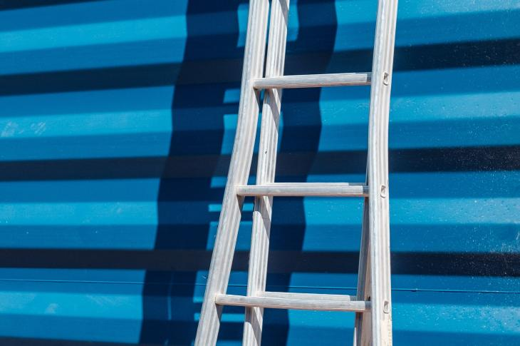 A ladder up against a blue shipping container