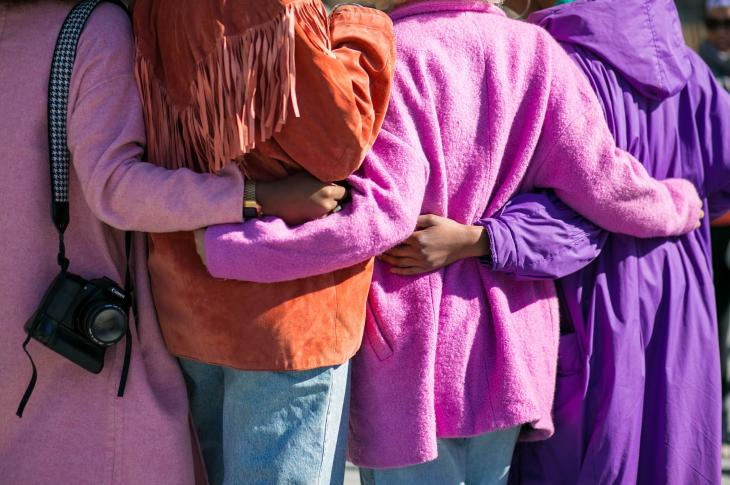 Women hugging with brightly colored coats on
