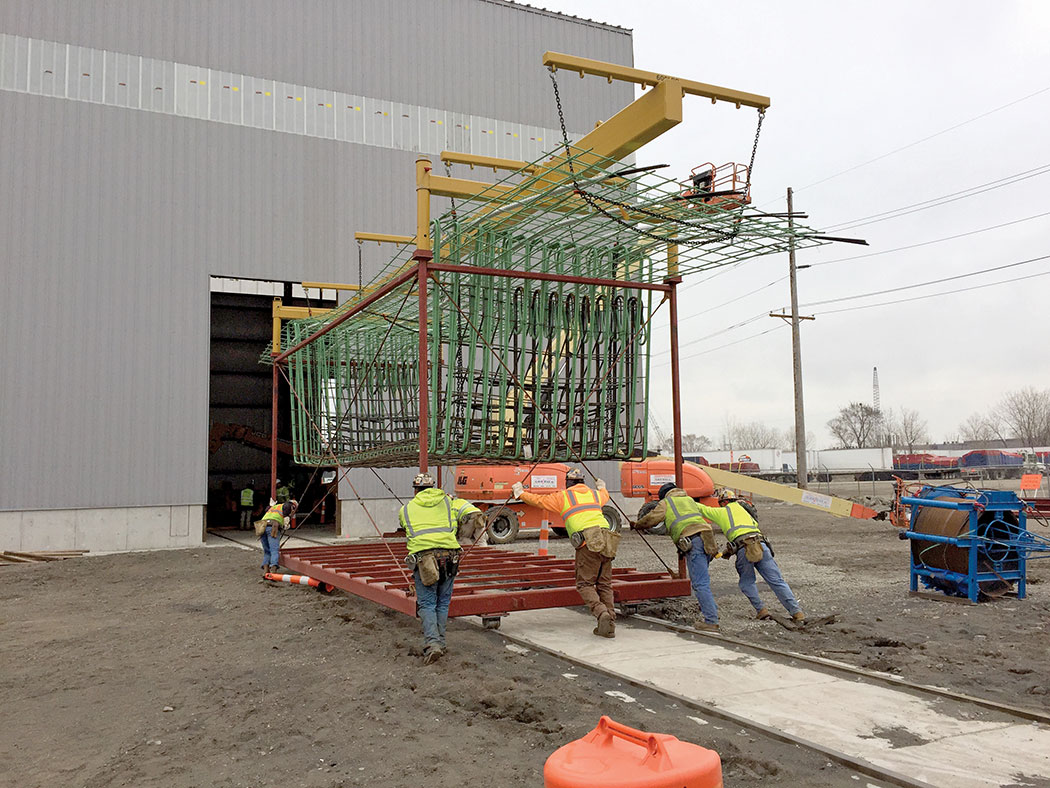 Crews rolling reinforcement cage into building for precast superstructure segments