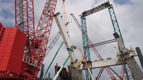 In effort to keep on schedule despite challenging in-river conditions, contractors have focused on building the segmental steel bridge arches.