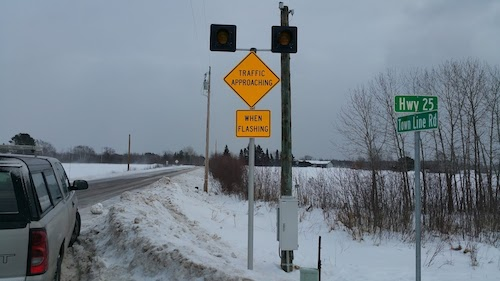 The warning messages along the minor road read TRAFFIC APPROACHING/WHEN FLASHING.