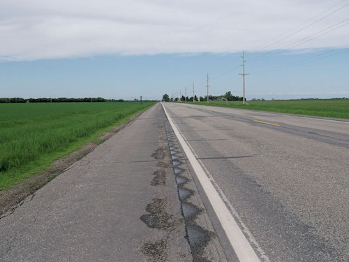 The design standards used for shoulder rumble strips were focused on state roadways, which usually have wider shoulders and total pavement width.