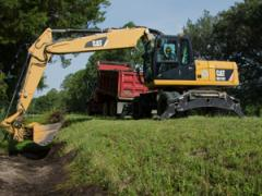 Cat M318D clears silt and grass from ditches along Florida State Highway 100.