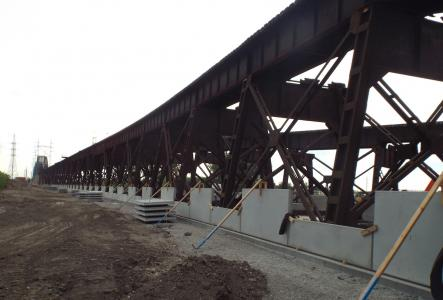 The first course of concrete panels are set and braced around the existing steel trestle.