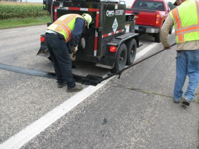 A view of workers repairing transverse cracks on County Road 13
