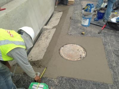 Construction crew member adjusting concrete final grade on a manhole riser.
