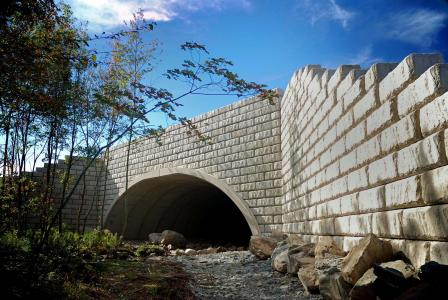 Vertical headwalls and wing walls for precast arch bridge construction