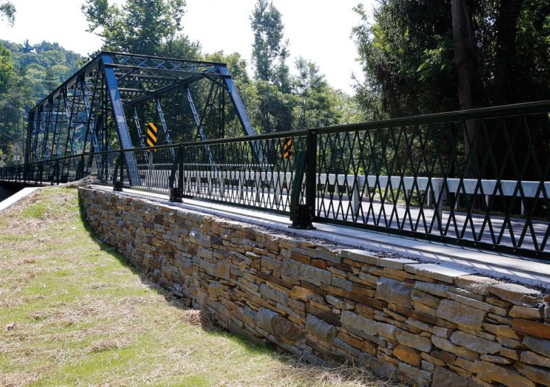 The Ithaca, N.Y., bridge is registered in the National Register of Historic Places; its original truss steel dates from the Model T era and had a 15-ton load restriction.