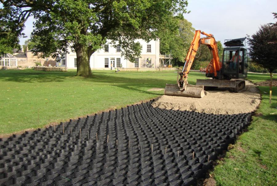 Soil confinement system supports access over soft subgrade, protects tree roots