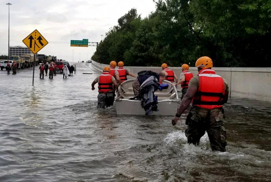 Texas Army National Guard members wade through rising Houston floodwaters.